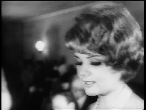 B/W 1961 close up smiling face of woman dancing the Twist on dance floor / newsreel