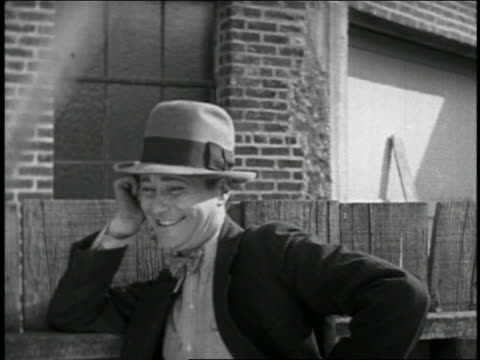b/w 1928 close up smiling man in hat getting hit on head with plank / short - plank stock videos & royalty-free footage