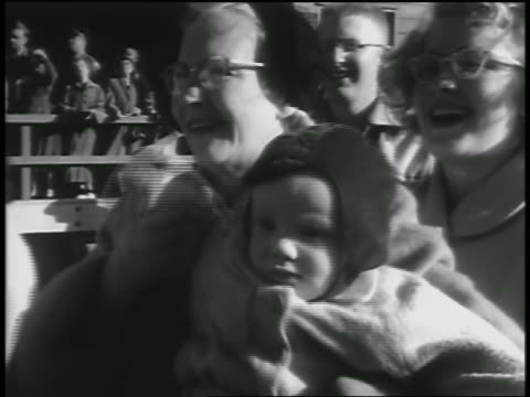 vídeos de stock e filmes b-roll de close up smiling senior woman holding baby + waving to returning soldiers / seattle - 1954