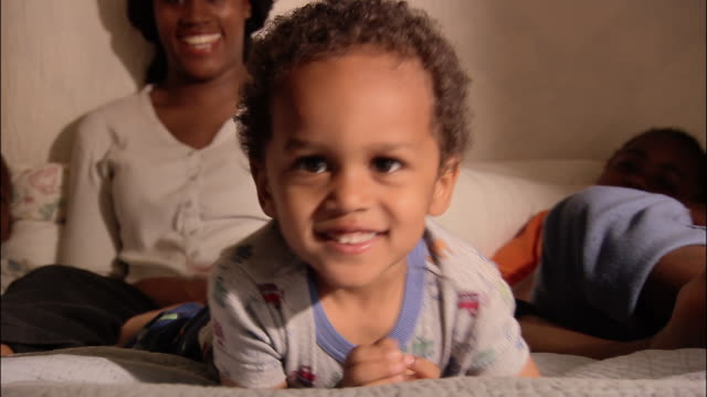close up smiling toddler lying on parents' bed with family / getting off bed - brother stock videos & royalty-free footage