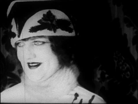 B/W 1922 close up smiling woman modeling Poiret hat + turning / newsreel