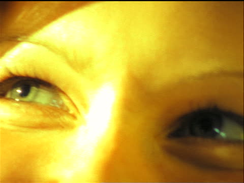 overexposed close up smiling woman's eyes looking up then to side / tilt down to mouth - overexposed stock videos & royalty-free footage