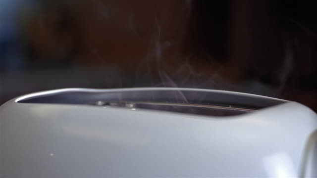 Close up smoke rising from pop-up toaster / slice of burnt toast popping up