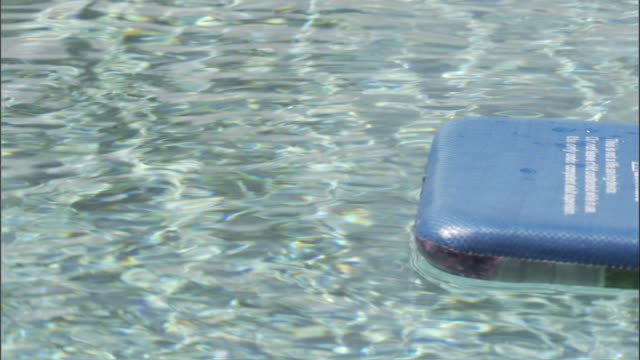 Close Up - Snake on board in swimming pool floats past camera /