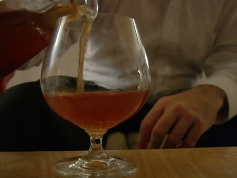 close up snifter being filled with brandy / man drinking / setting  down empty glass - brandy snifter stock videos and b-roll footage