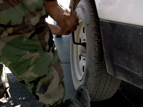 close up soldier changing tire on truck/ afghanistan - lug wrench stock videos and b-roll footage