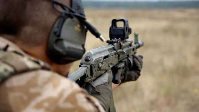 close up soldier shooting an automatic rifle at testing ground in field - shooting a weapon stock videos & royalty-free footage