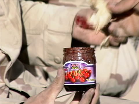 Close up soldiers dipping food in jar of cranberry sauce/ Afghanistan