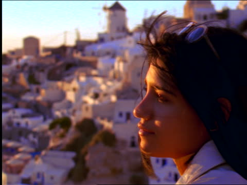 close up somber woman at sunset / out of focus buildings in background / santorini, cyclades islands, greece - santorini stock videos & royalty-free footage