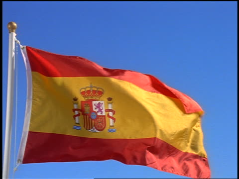 close up pan spanish flag blowing in wind / blue sky in background - spanish flag stock videos and b-roll footage