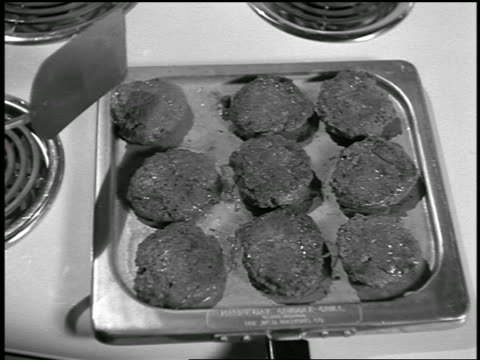 b/w 1955 close up spatula flipping burgers on griddle on stove / commercial - グリルパン点の映像素材/bロール