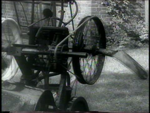 vídeos y material grabado en eventos de stock de b/w 1960 close up spinning experimental contraption on lawn with spraying hose + shovel attached / newsreel - invento