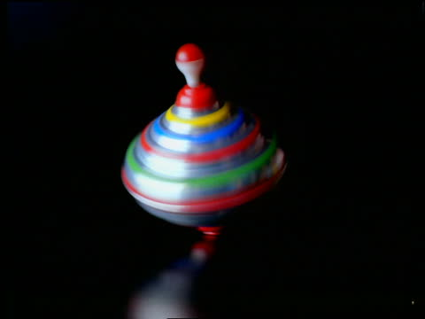 vídeos y material grabado en eventos de stock de close up spinning top with black background - enfoque de objetos sobre la mesa