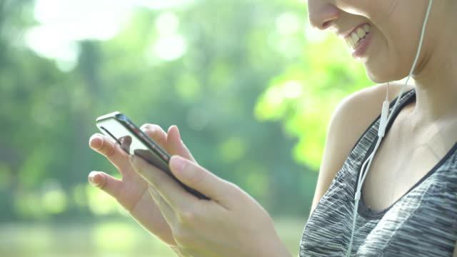 vídeos de stock, filmes e b-roll de close-up mulher esporte usando telefone celular - sutiã para esportes