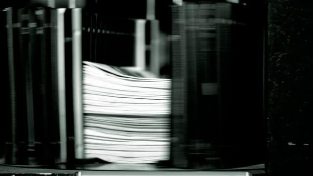 Close up stacks of Santa Barbara News Press being fed into machinery to be bundled / Santa Barbara, California