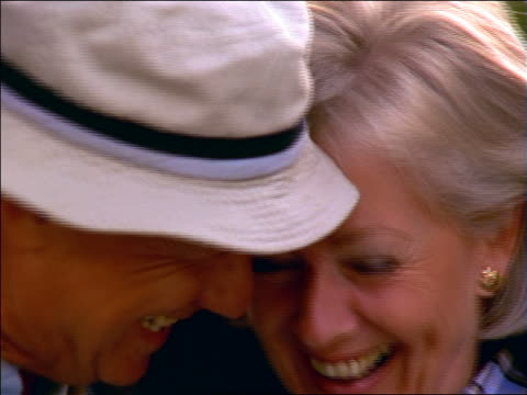 close up standing senior couple smiling + cuddling outdoors / france - sonnenhut stock-videos und b-roll-filmmaterial