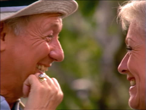 close up standing senior couple smiling outdoors / woman touches man's nose / france - mature couple stock videos & royalty-free footage