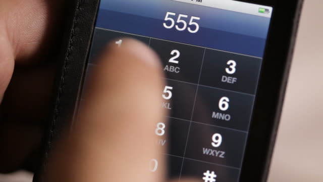 Close Up static , A caller dials a phone number on a touch,screen cell phone. /