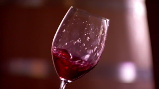 close up static - a hand tilts a wine glass filled with red wine. / sicily, italy - bicchiere da vino video stock e b–roll