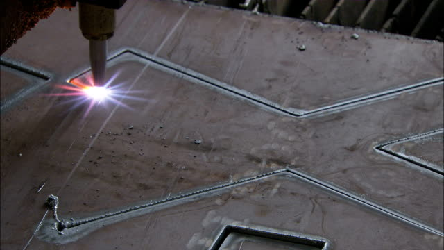 Close Up static - A laser cuts an X into a sheet of steel./Shanghai, China