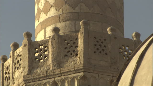 close up, static - a man clothed in white walks around the base of a mosque tower / egypt - intricacy stock videos & royalty-free footage