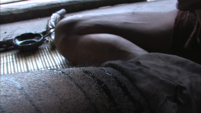 Close Up static - An artist uses a hammer and nail to tattoo a man's skin. / Indonesia