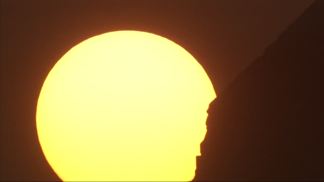 close up, static  - the sun glows as it rises behind a pyramid / egypt - egypt stock videos & royalty-free footage