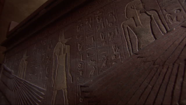 Close Up, static - The walls of a tomb feature Egyptian figures and hieroglyphics