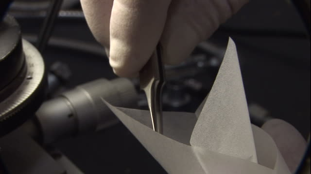 Close Up static - Tweezers place particles into a paper receptacle. / USA