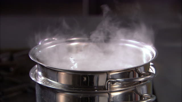 close up steam rising from double boiler / chef lifting spaghetti out of pot and testing firmness / auckland - spaghetti video stock e b–roll