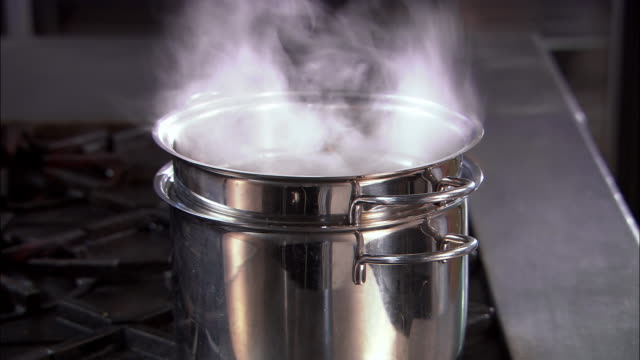 Close up steam rising from double boiler on stove / Auckland, New Zealand