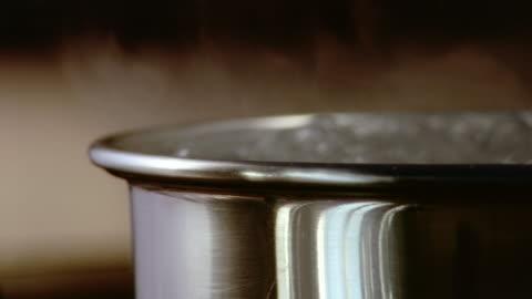 vídeos y material grabado en eventos de stock de close up steam rising from pot of boiling water / london - hervir