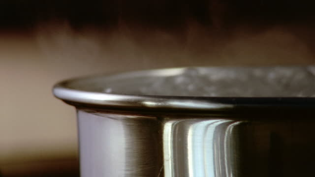 stockvideo's en b-roll-footage met close up steam rising from pot of boiling water / london - pannen