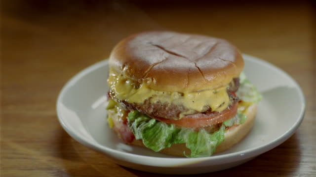close up steaming cheeseburger on a plate - cheeseburger stock videos & royalty-free footage