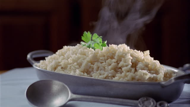 Close up steaming dish of brown rice