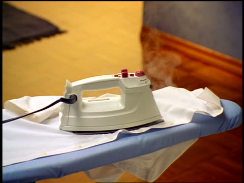 close up steaming iron lying on shirt on ironing board - iron appliance stock videos & royalty-free footage