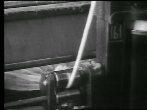 B/W 1922 close up strand of cotton on machinery in cotton mill / newsreel