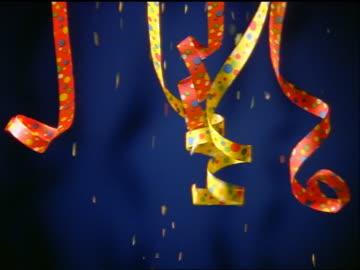 close up streamers + confetti falling from above with blue background - konfetti bildbanksvideor och videomaterial från bakom kulisserna