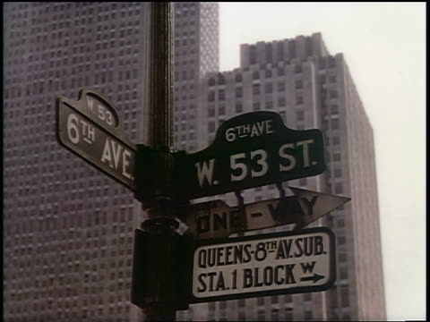 1939 close up street signs at intersection of sixth avenue + 53rd street / new york city / industrial - 道路名の標識点の映像素材/bロール