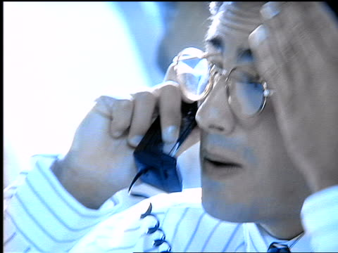 blue close up stressed hispanic man with eyeglasses talking on telephone with hand on forehead - nur männer über 30 stock-videos und b-roll-filmmaterial