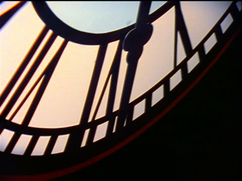 close up stretching silhouetted clock hand moving - inquadratura dall'alto di un tavolo video stock e b–roll