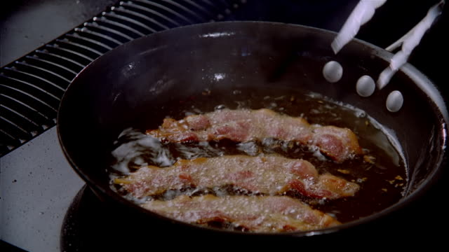 close up strips of bacon frying in pan / being removed from pan with tongs / zoom grease in empty pan - 調理鍋点の映像素材/bロール