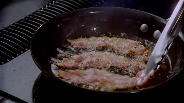close up strips of bacon frying in pan / zoom in being turned over with tongs - bacon stock videos and b-roll footage