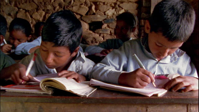 close up students writing in small classroom within stone building / nepal - developing countries stock videos & royalty-free footage