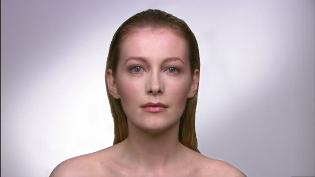 stockvideo's en b-roll-footage met close up studio portrait of younger womanmorphing into an older woman - ontbloot bovenlichaam