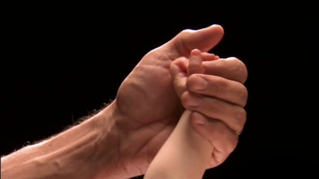 Close up studio shot of father's hand holding baby's hand