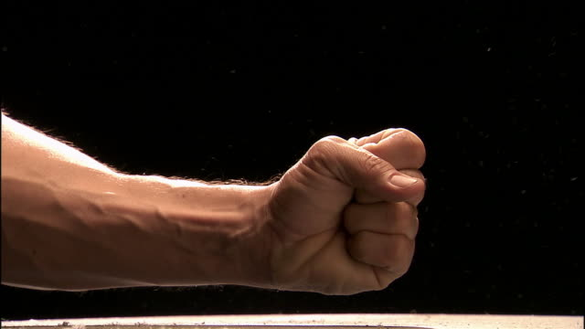 Close up studio shot of man's fist / pounding on dusty surface