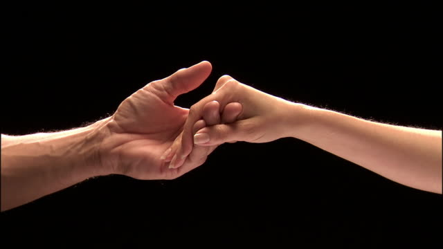 Close up studio shot of man's hand and woman's hand reaching toward each other / holding hands / letting go