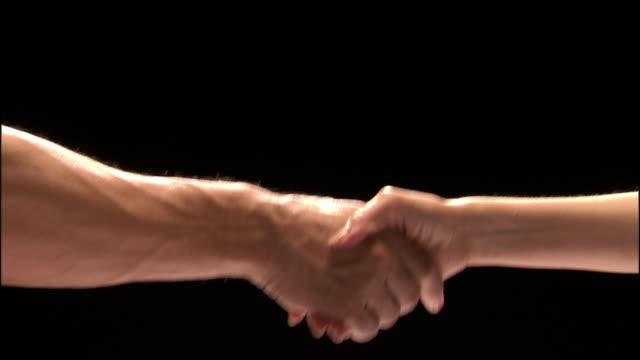 close up studio shot of man's hand and woman's hand shaking hands - sfondo nero video stock e b–roll