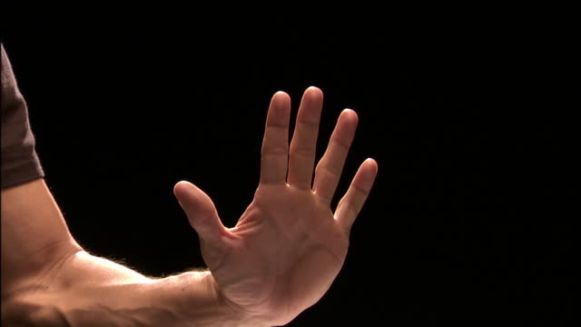 Close up studio shot of man's hand giving sign to halt